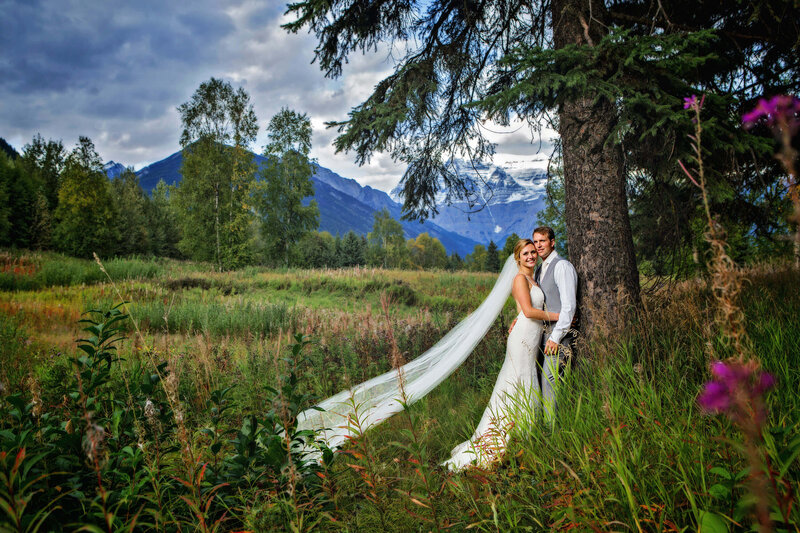 bride and groom lean on tree with mountains behind