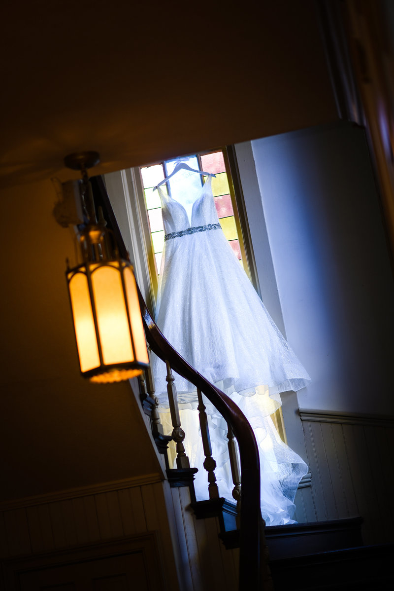 Beautiful Wedding Photography: Bridal gown hands on staircase with stained glass, First Baptist Church of Starkville