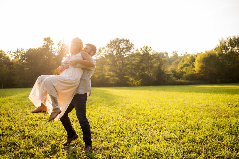 Couple running and playing in a field at golden hour in lafayette indiana