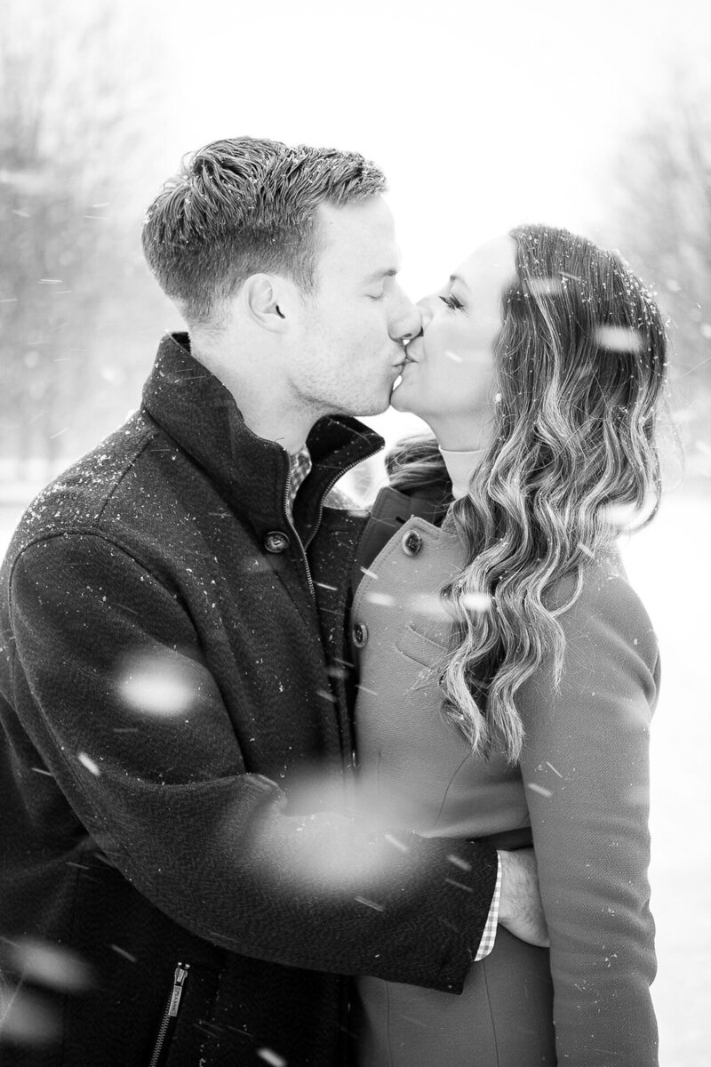 couple kiss during snowy winter engagement session in Millennium Park Chicago