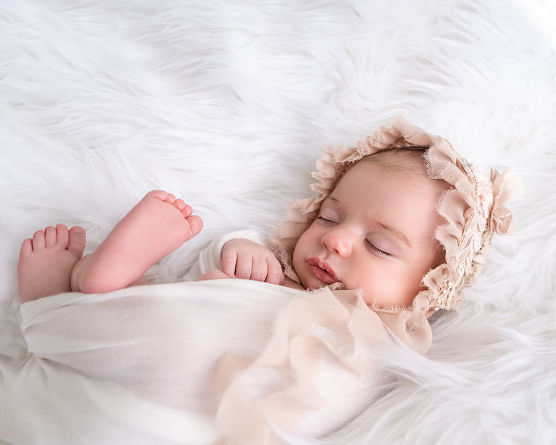 newborn photography session with newborn girl sleeping on a white fur blanket