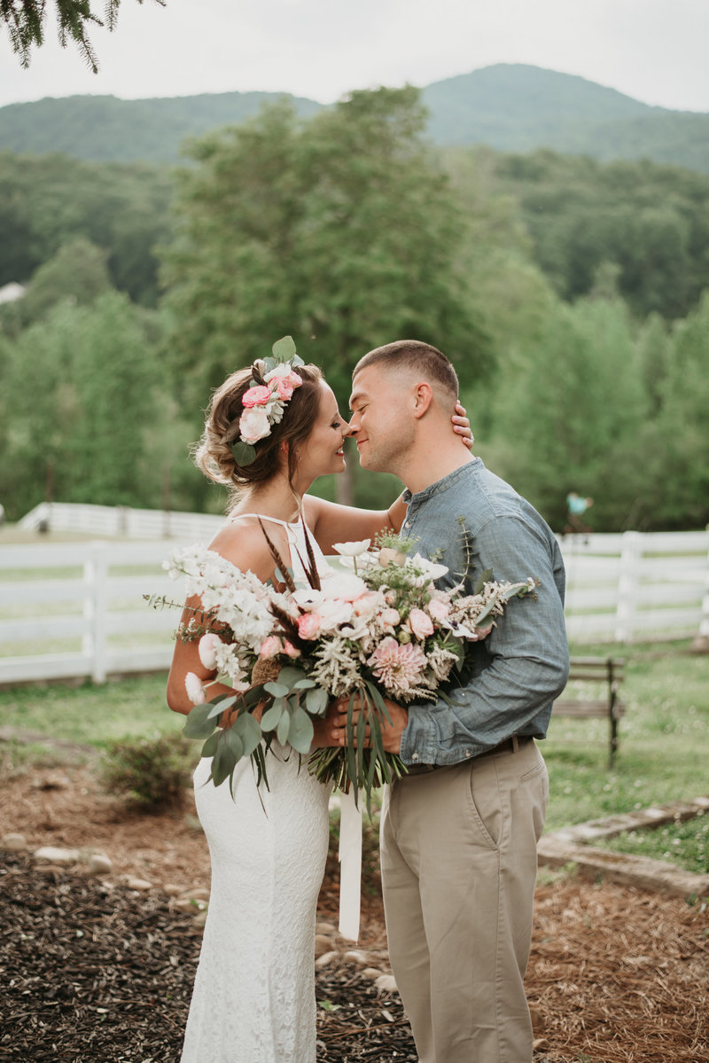 Couple kissing in the mountain on their wedding day with flower bouquet
