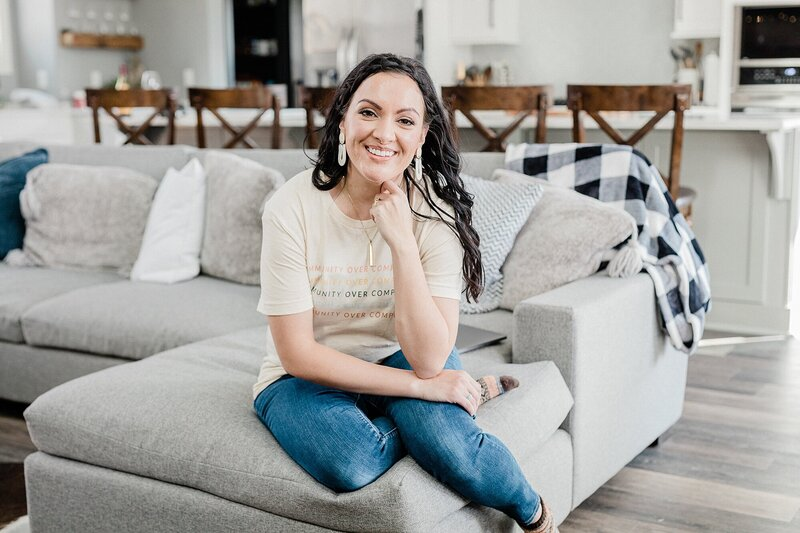 Dolly of Dolly DeLong Photography a Nashville Branding Photographer Sitting on a Cream Couch Smiling at the camera wearing a community over competition t shirt for her branding photo shoot