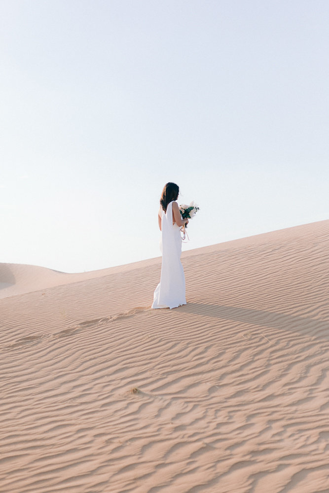 bride walking in the sand during sunset in the desert of dubai for her wedding
