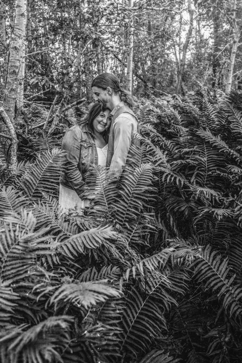 engaged couple embraces  in wild ferns