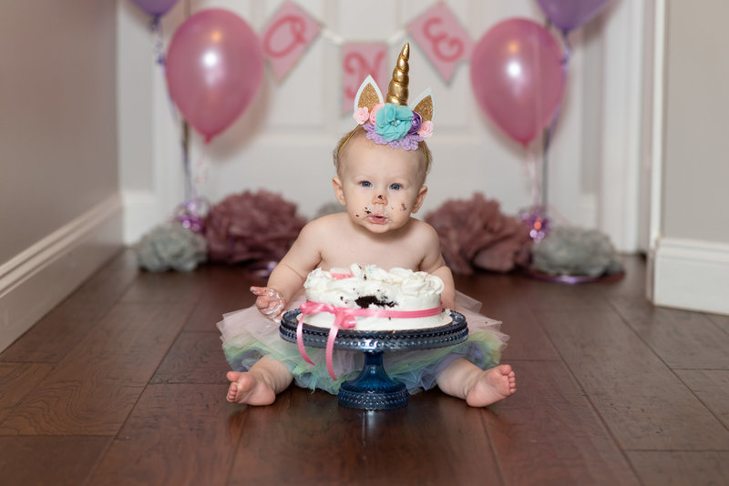 One year old girl smashing cake wearing unicorn headband