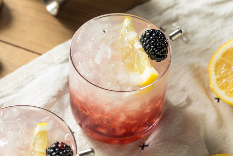 Cocktail garnished with blackberry & lemon