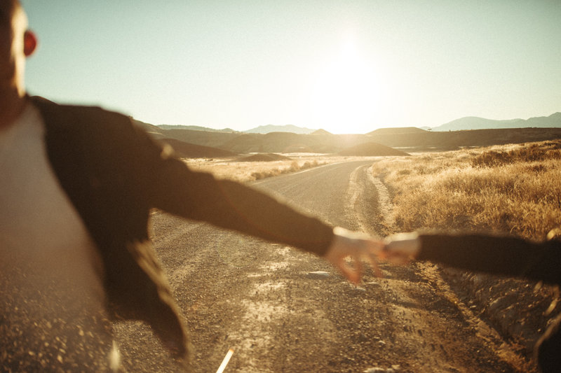 two people holding hands on dirt road