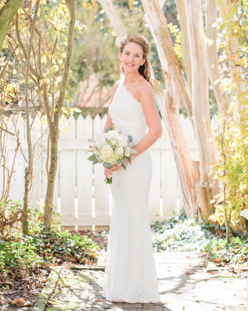 bride smiling in her one shoulder lace dress at her colonial williamsburg wedding