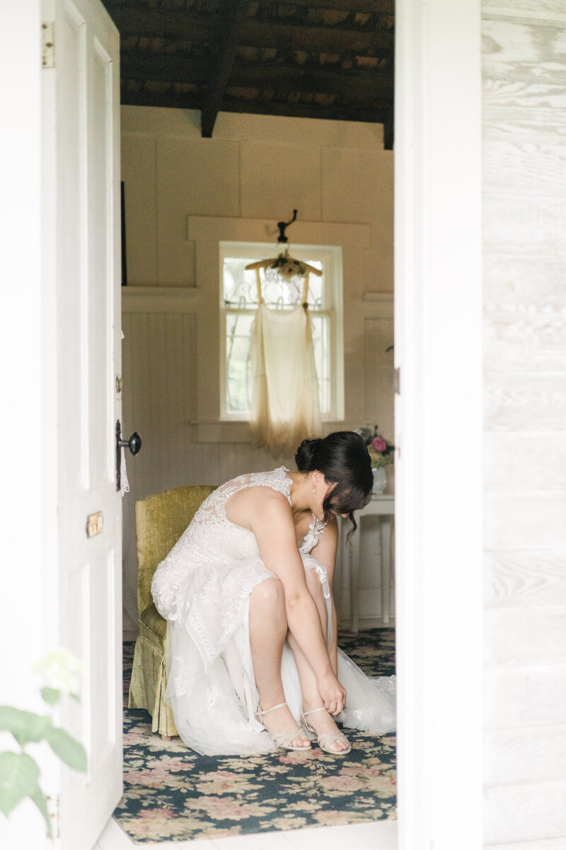 bride sitting down putting on her shoes