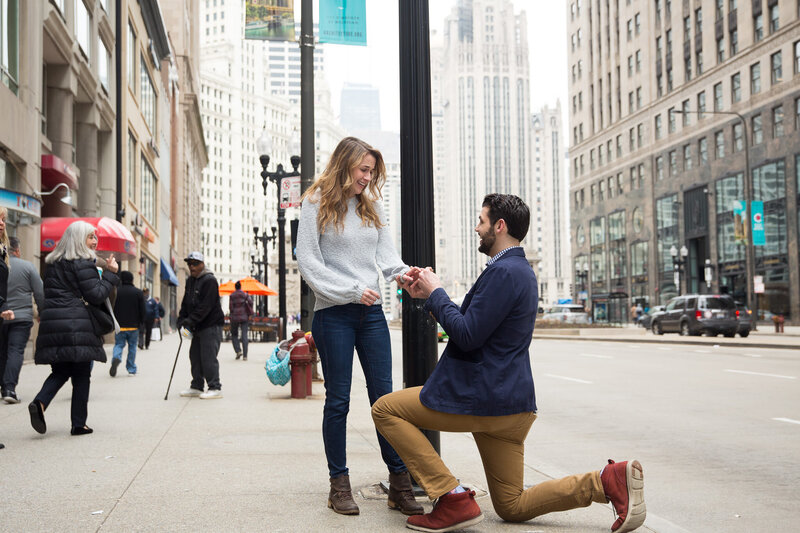 man on one knee proposing downtown chicago mag mile