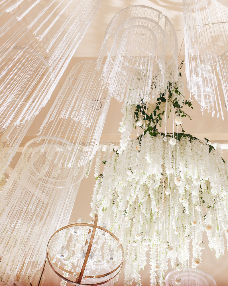 Hanging wedding decor made of white ribbons on hoops to create a stunning centrepiece at a high-end luxury part.