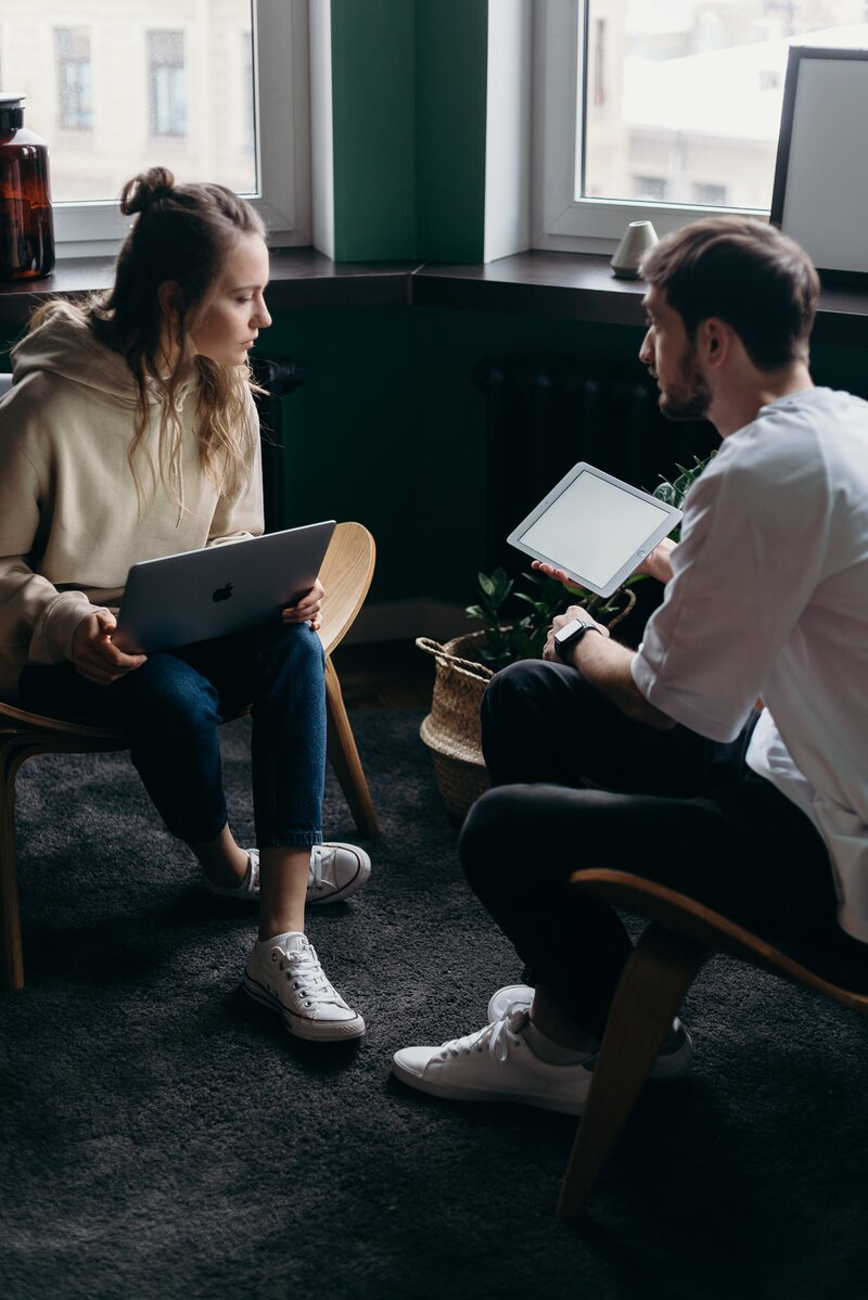 photo-of-couple-talking-while-holding-laptop-and-ipad-4065158