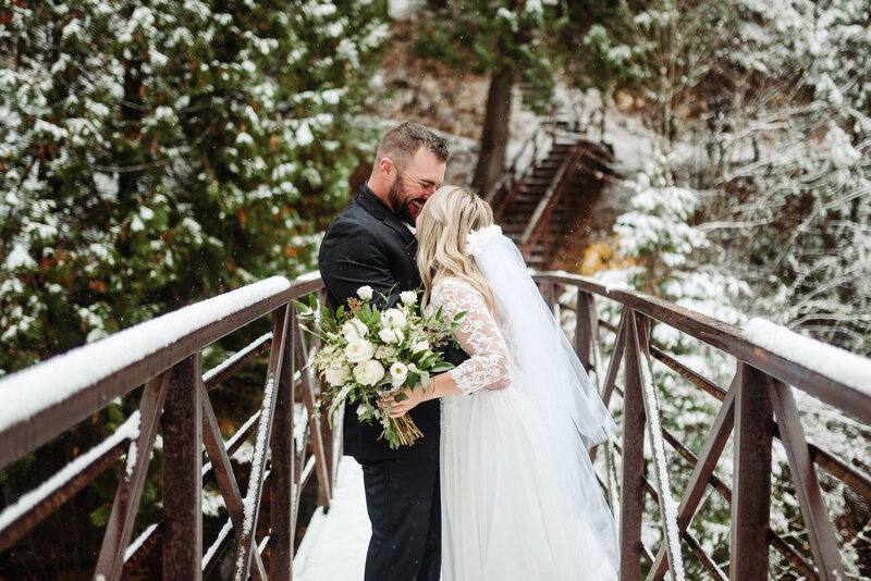 bride & groom lean in for a kiss on a bridge covered in snow