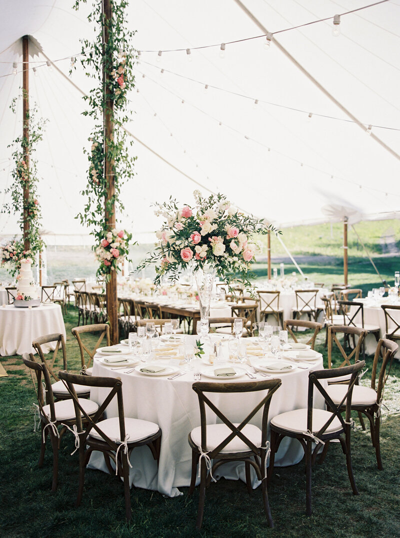 testimonial photo, empty tented reception featuring tall bouquets of pink flowers, foliage and pink flowers decorate wooden tent poles