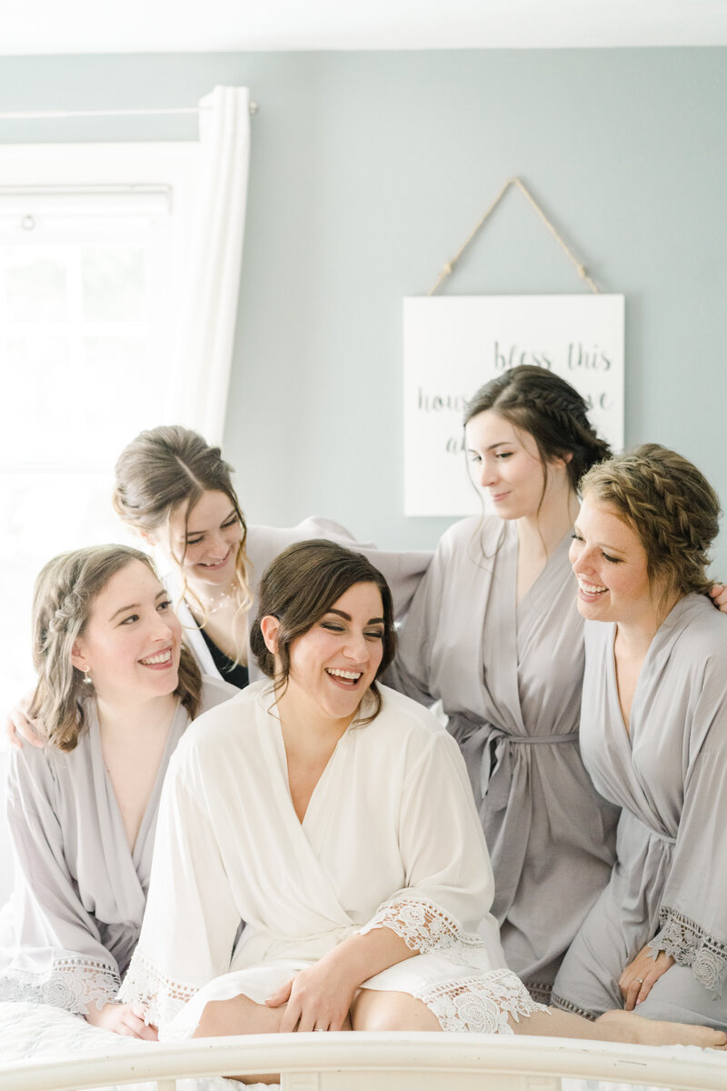 bride and bridesmaids on bed looking at each other and laughing