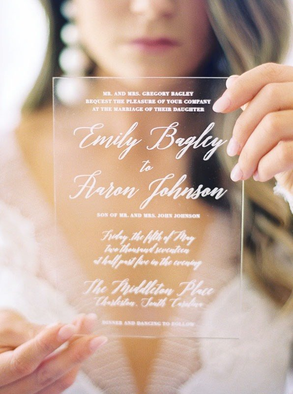 bride holding up clear invitations