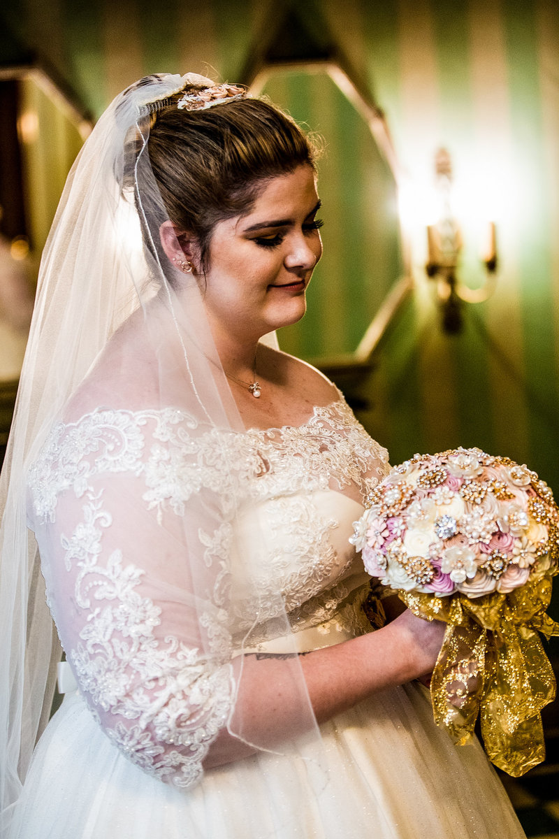 Bride poses with her bouquet in the ladies lounge before her wedding at the Warner Theatre