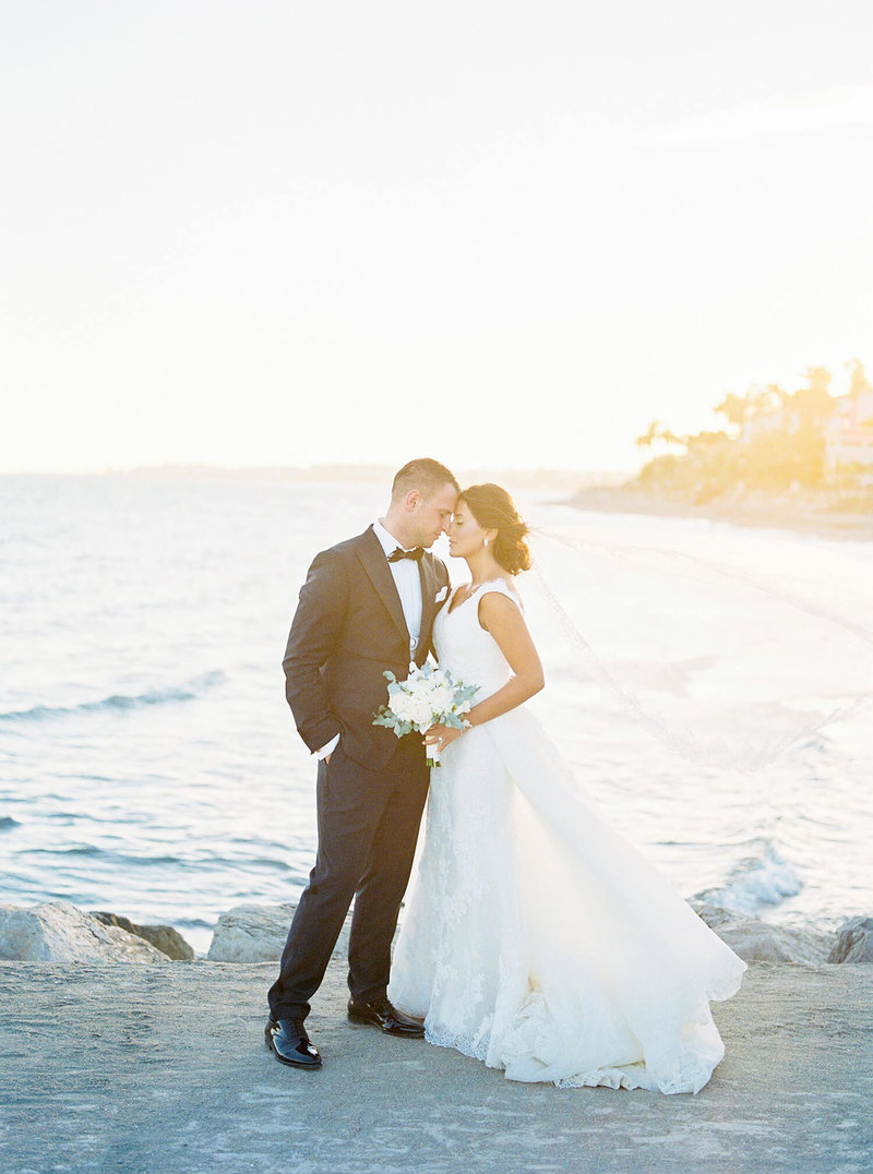 Bride & groom embrace in front of an ocean at the sun sets into the water