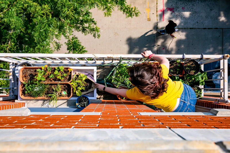 Woman checks her plants on her apartment balcony