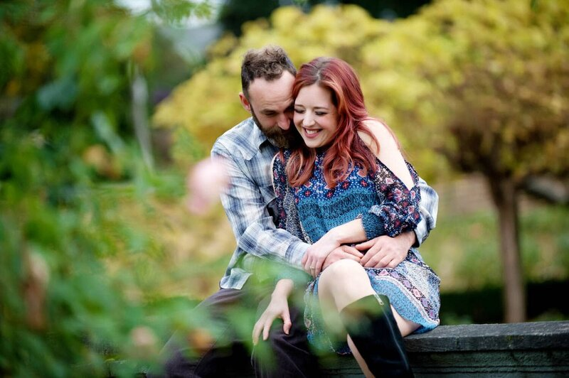 a man and a woman with red hair hug while sitting on a wall during their engagement photos at peninsula park in the fall