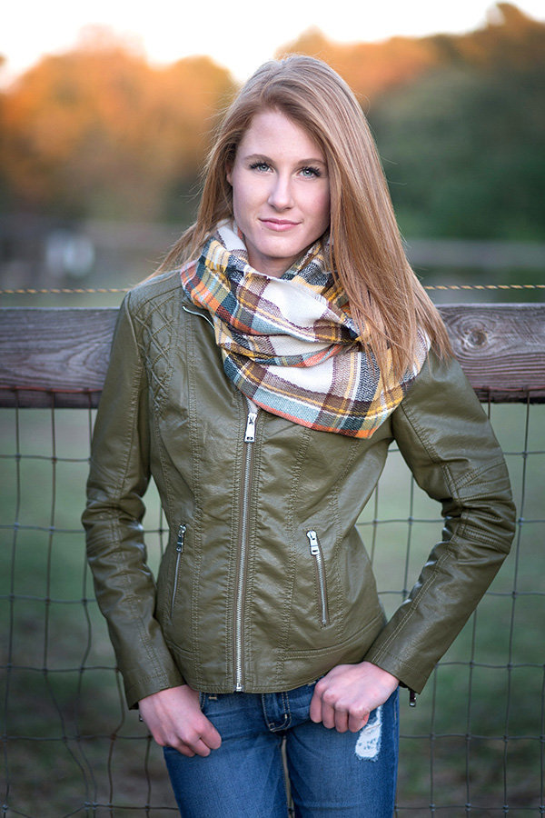 High school senior girl smiles in green leather jacket and scarf for senior portraits