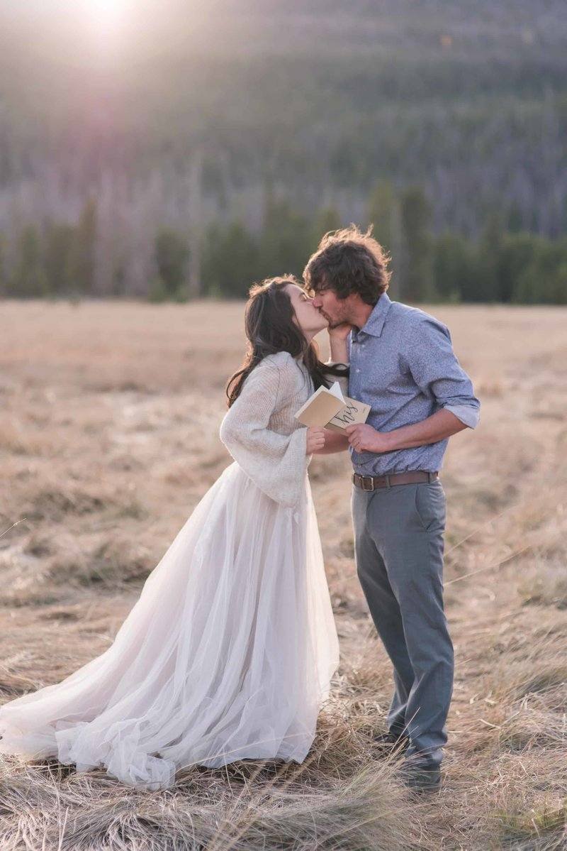 "Texas elopement photographer captures Georgia couple eloping in Colorado at Rocky Mountain National Park holding vow books as they share their ""first kiss."""