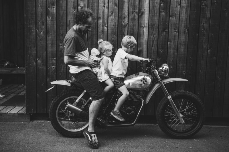Dad and kids sitting on a motorcycle together