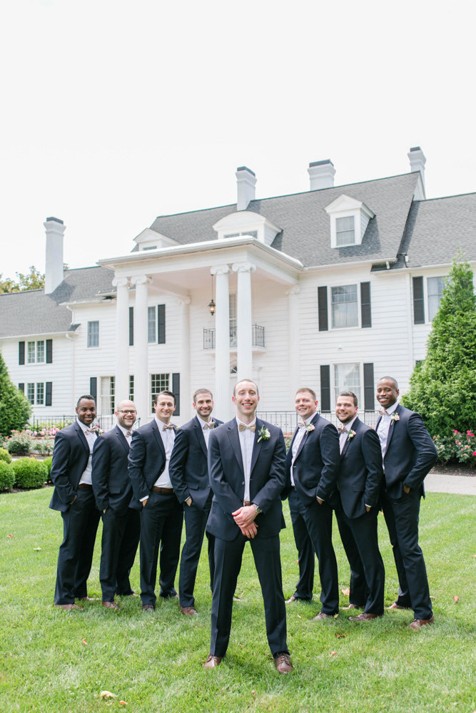 groomsmen standing in front of manor at eastern shore wedding at kirkland manor by costola photography