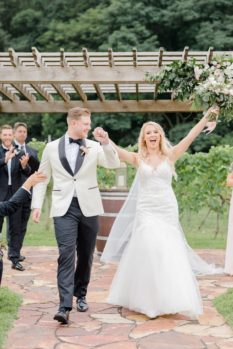 bride and groom excited leaving ceremony at Running Hare Vineyard Wedding photographer costola photography