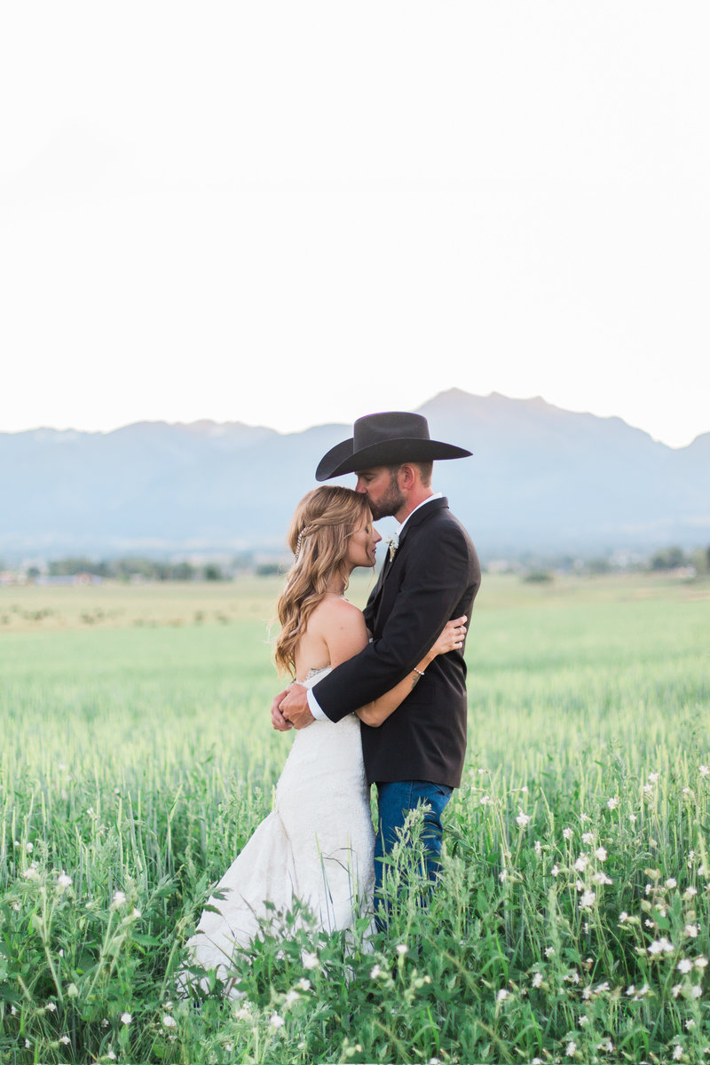 cowboy groom kissing bride in mountains