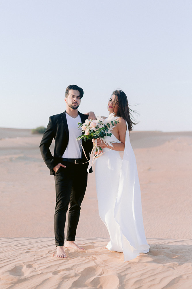 couple posing in front of the camera during a photoshoot in the desert of dubai