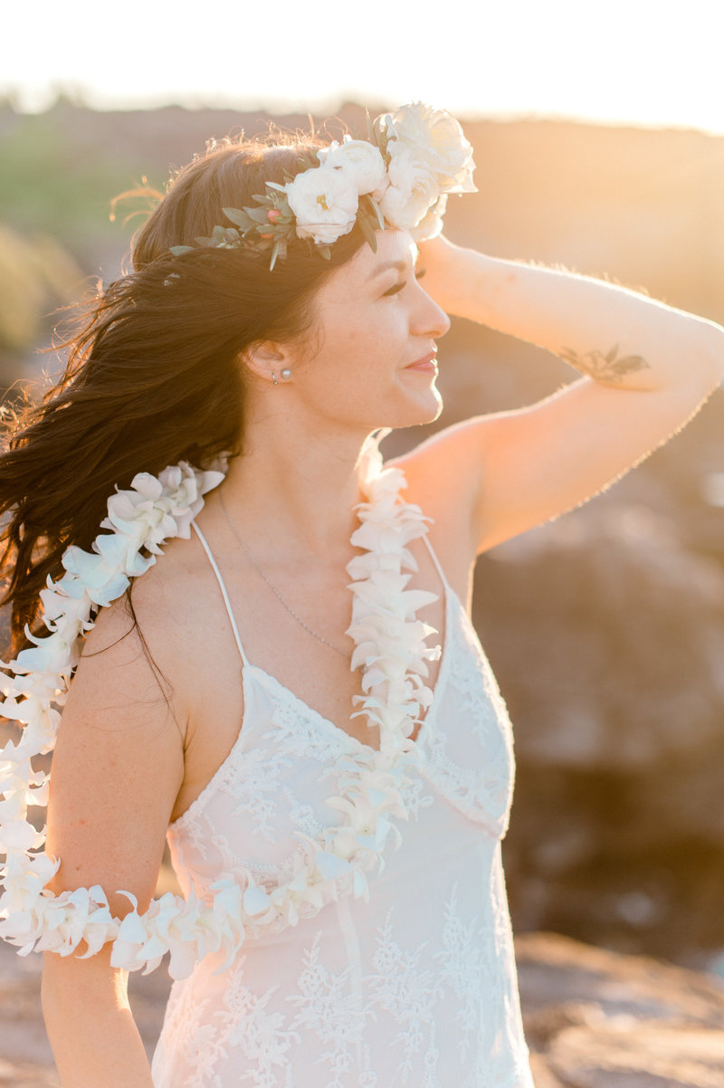 Bride wearing a white lei pohaku flower crown and white lei on her wedding day in Maui