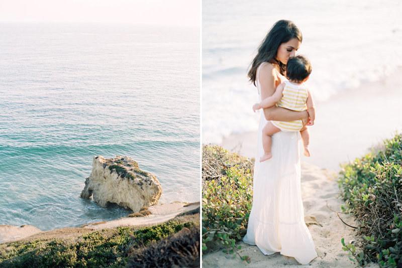 A mother in a white dress snuggles her baby on the cliffs overlooking the ocean in Malibu