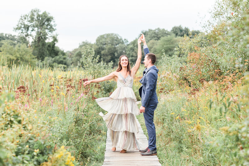 woman twirling in her dress in wildflower field