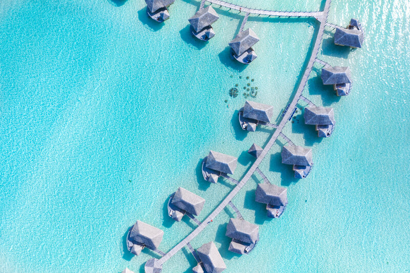 Aerial view on a couple in their overwater bungalow in Bora Bora