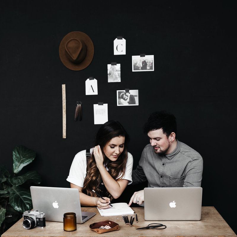 A+C-brandshoot-13-WEB-seattle-wedding-photographers-black-wall-hat-desk-layout-laugh-candid-couple-goals-cute-work-together-business-photo-feather-ruler-plan