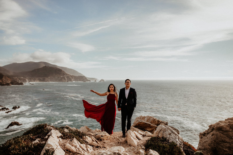 man and woman standing on rocks next to ocean