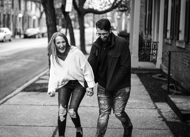 Engaged couple laughing as they walk along State Street in Erie, PA