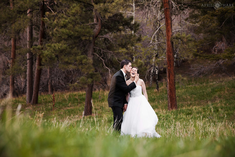 Groom kisses his bride in the forest at The Pines at Genesee