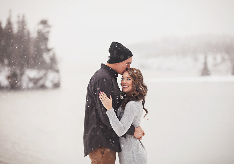 Engaged couple are hugging in field of snow.  Flakes are drifting down.