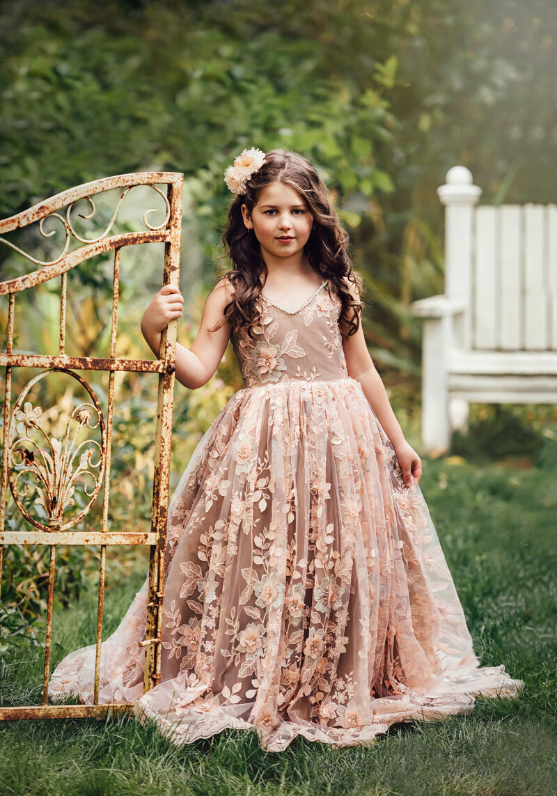 Young girl poses by a metal gate in beautiful lace dress