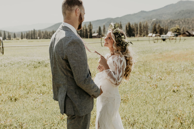 Bohemian bride smiles at groom while pulling on his tie at Mountain Springs Lodge in Levenworth, WA