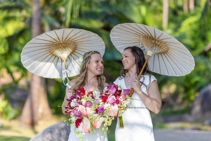 Two brides with parasols on beach