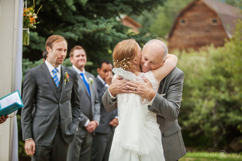Bride hugs dad at her outdoor Colorado mountain wedding ceremony with a barn