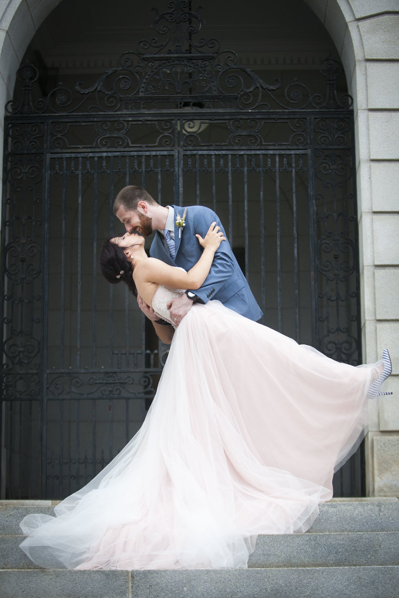 Groom dips bride for a kiss after their wedding in front of Portland City Hall in Portland, Maine