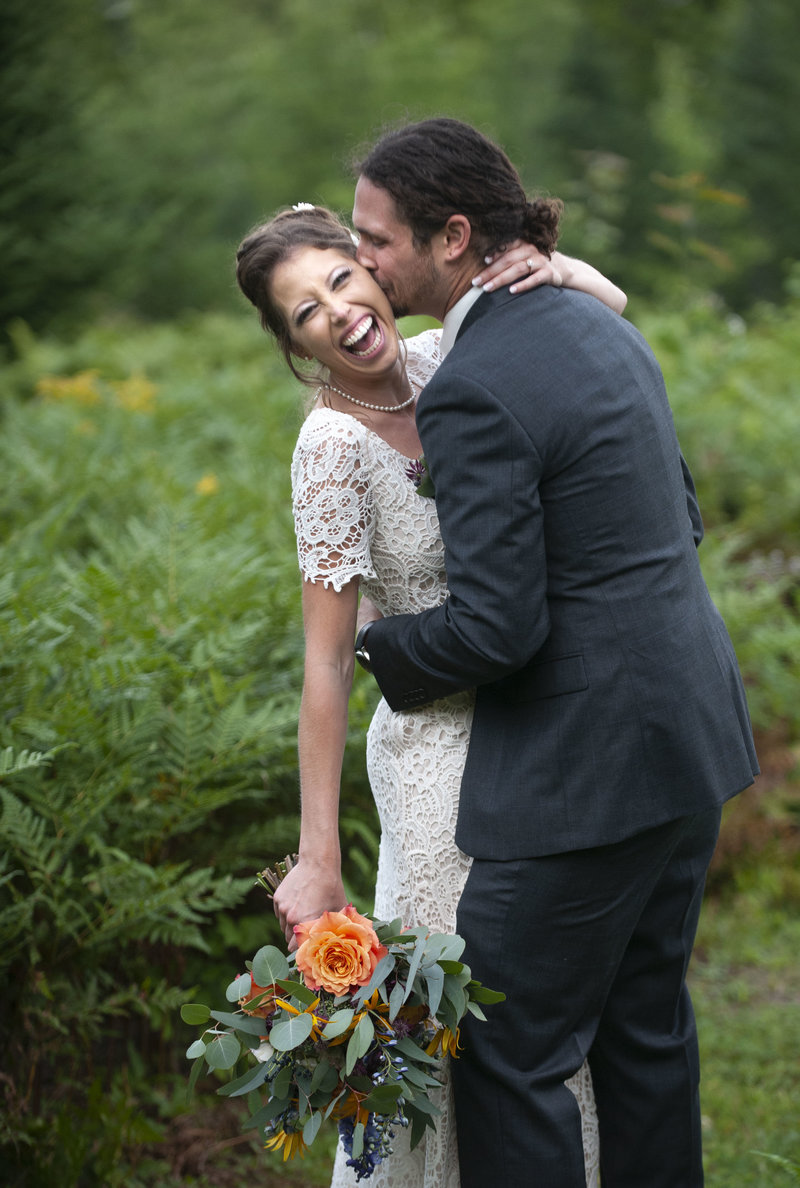 Bride & groom laugh & smile in a field at their Otisfield, Maine wedding