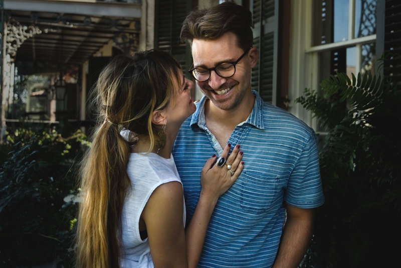 Couple poses on balcony of French Quarter for their engagement session