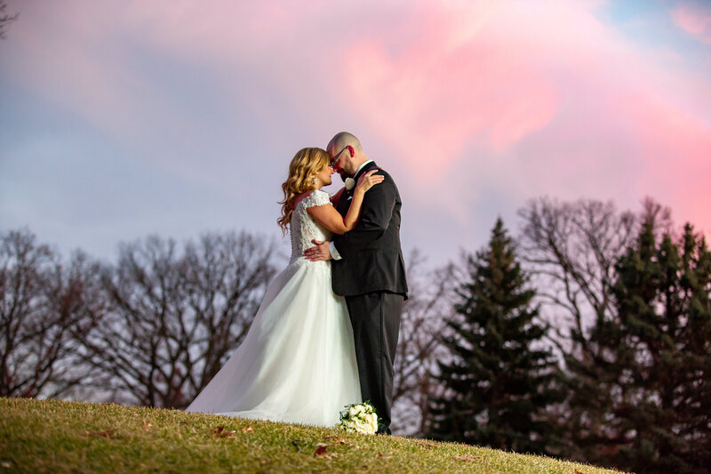 A bride and groom posing on a hill with dramatic sunset on the background.