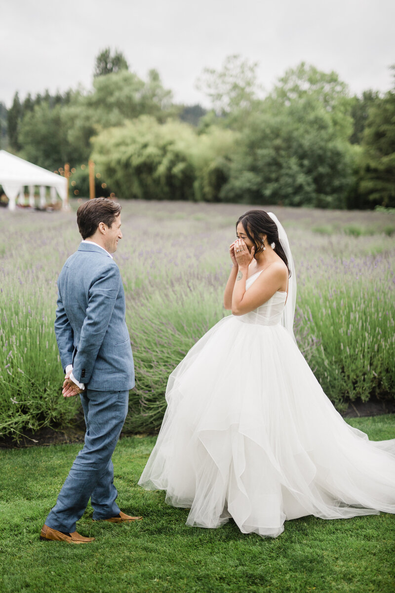 bride viewing her groom for the first time on her wedding day and tearing up with emotions. She is in a lavender field at a wedding venue in portland